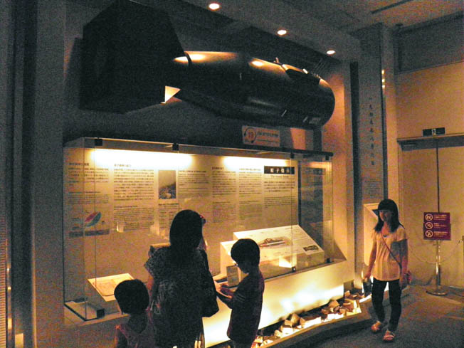 "A full-size replica of the ""Little Boy"" atomic bomb is suspended above a display case in the Hiroshima Peace Memorial Museum."