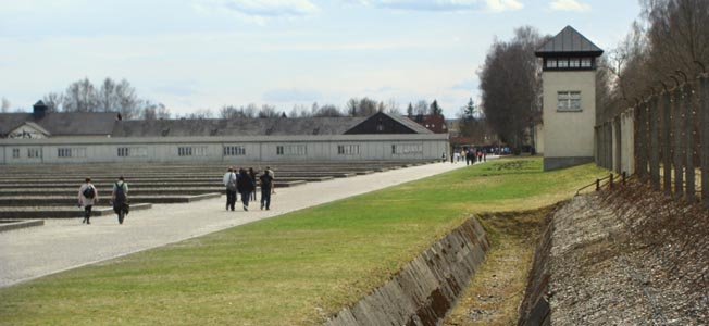 Footprints of the barracks (left), a partially filled in moat, sinister guard tower, and barbed-wire fence silently remind visitors of the cheapness of life at Dachau.