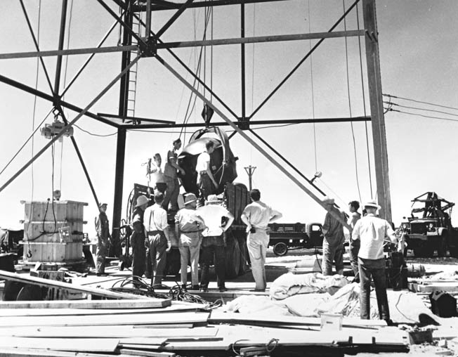 "The Trinity test bomb, known as the ""gadget,"" is carefully winched to the top of a 100-foot tower for the final assembly at the Alamogordo Bombing and Gunnery Range, New Mexico."