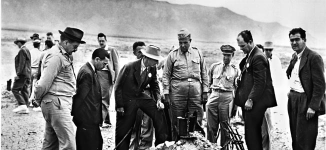 Project director Robert Oppenheimer (with hat, center), Brig. Gen. Leslie Groves (center), and others inspect the melted remains of the test tower at ground zero after the Trinity blast. The photo was taken in September when some participants returned for news reporters. Note men wearing shoe covers to keep from picking up radiation.