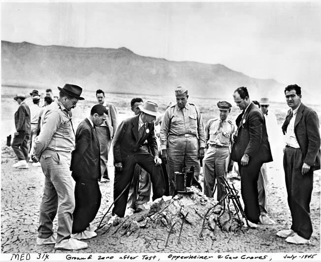 Oppenheimer (center, with light colored hat ), General Leslie Groves (to Oppenheimer's left), and others inspect the ground zero site of the Trinity test, September 1945, after Japan's surrender.