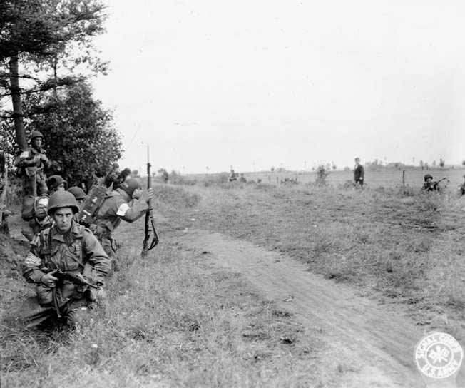 Anticipating contact with German forces at any moment, paratroopers of the 101st Airborne Division gather along a treeline in the Dutch countryside on September 18, 1944. German small arms fire and the deadly accurate 88mm cannon inflicted heavy casualties on the Americans assaulting Best.