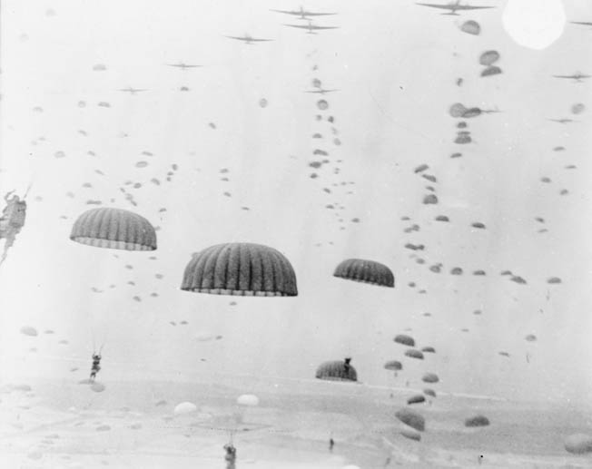 American airborne troops, their parachutes billowing in the sunlight, plummet toward the ground below during the opening phase of Operation Market-Garden.