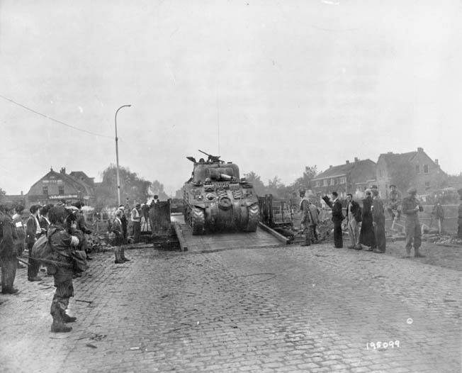A British Sherman tank crosses the Wilhelmina Canal in Holland as American paratroopers of the 101st Airborne Division and Dutch civilians look on. Allied control of the Wilhelmina Canal was critical to the advance of ground forces toward British paratroopers at Arnhem.