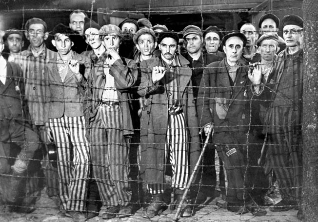 Hollow-eyed, emaciated male prisoners, victims of Nazi genocide against Jews of Europe, gripping barbed wire fence in wonderment at their liberation by American forces from the cruelties of Buchenwald concentration camp.