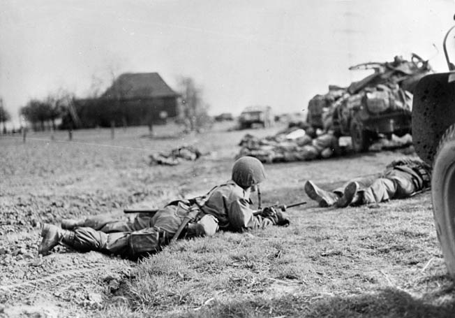 17th Airborne Division paratroopers are pinned down by German fire shortly after landing. One trooper (right) appears to be lying dead on his back.