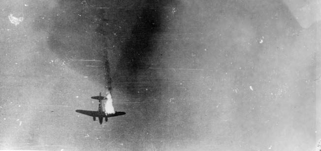 An American transport plane, its right wing aflame, plunges to its doom; 72 aircraft were lost on the mission.