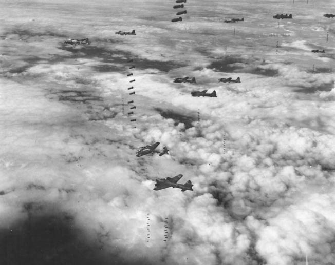 During a heavy raid on Magdeburg, Germany, in September 1944, Boeing B-17 bombers of the U.S. Eighth Air Force drop their sticks of bombs almost simultaneously as they brave flak and enemy fighters to remain on course for an accurate bomb drop. Magdeburg and other major German cities were well protected by the Luftwaffe in the air and by flak units on the ground.