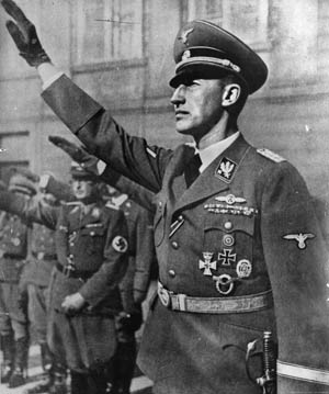 In full uniform and regalia, Reich Protector of Bohemia and Moravia Reinhard Heydrich gives a stiff Nazi salute during an official party function.