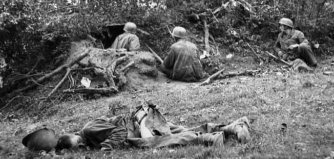 With the body of a dead American soldier lying nearby, three elite German paratroopers wait quietly in a well concealed defensive position along a Norman hedgerow. Bundesarchiv Bild 101I-586-2215-25A, Photo: Reich