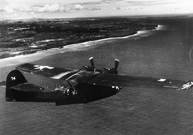 "A PBY-5 Catalina flying boat from a ""Black Cat"" night patrol squadron overflies the shoreline of New Guinea."