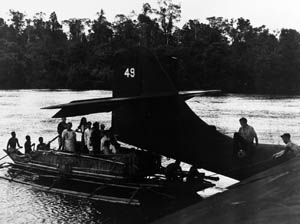 Women and children in an outrigger canoe prepare to be rescued by a PBY-5 in northwestern New Guinea.