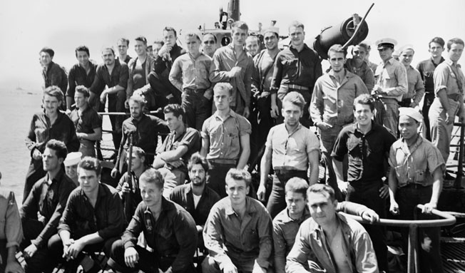 After their baptism of fire at Makin, some members of the 2nd Marine Raider Battalion bear the stoic gaze of combat veterans aboard the submarine USS Nautilus as they enter Pearl Harbor on August 25, 1942. A Marine at left is holding a captured Japanese Arisaka rifle.