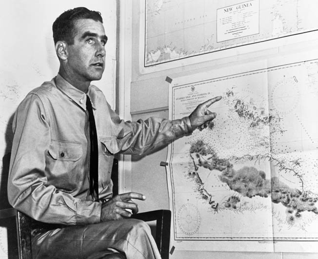 Lieutenant Commander Harry B. Heneberger, gunnery officer aboard the cruiser USS Quincy during the Battle of Savo Island, points to a map as he describes the abortive engagement after the battle had ended.