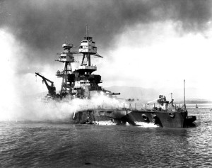 The only capital ship of the U.S. Navy to get underway during the attack on Pearl Harbor, the battleship USS Nevada lies beached at Hospital Point and on fire after taking several bomb hits. The Nevada was repaired and returned to service, bombarding German shore installations during the D-Day landings in France.