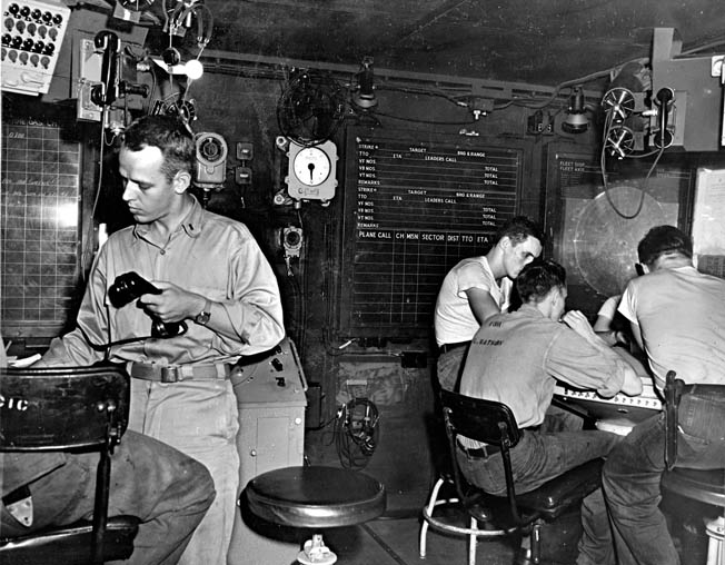 On the alert for approaching aircraft, an officer and enlisted sailors man the carrier's radar plot during the invasion of Leyte, November 1944.