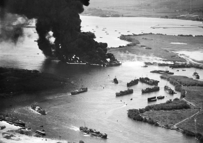 This aerial view of Pearl Harbor's West Loch in flames clearly shows burning LSTS at Tares 8 and 9 while other LSTs attempt to rapidly maneuver away from the conflagration toward safety.