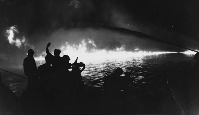 As night falls on May 21, 1944, sailors silhouetted against the flames across the West Loch of Pearl Harbor attempt to suppress the raging fires that have consumed numerous LSTs, LCTs, and LVTs.