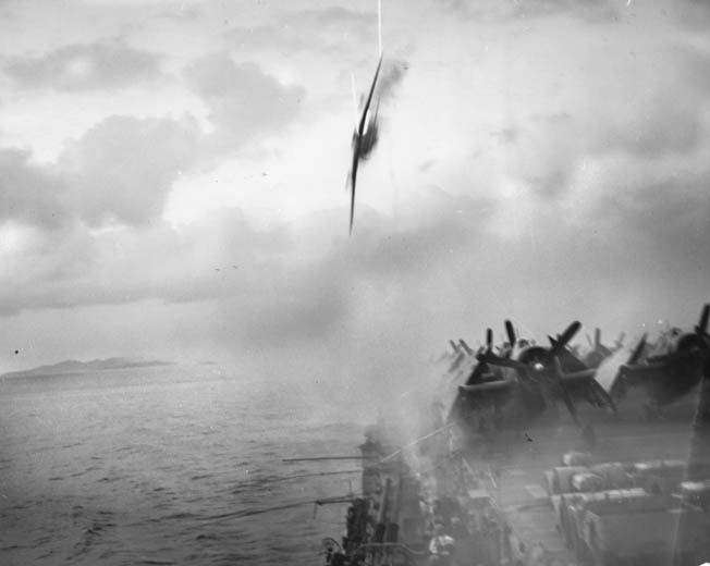 The escort carrier USS Sangamon (CVE-26), operating near Okinawa, survives a near-miss by a kamikaze pilot, May 4, 1945. Another kamikaze attack later that day hit home, however, and caused extensive damage.
