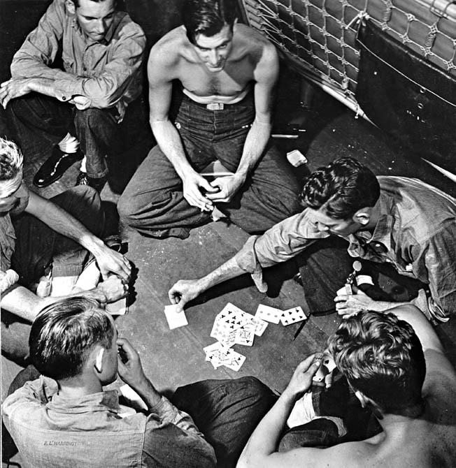 Killing time between battles, Yorktown crewmen play cards.