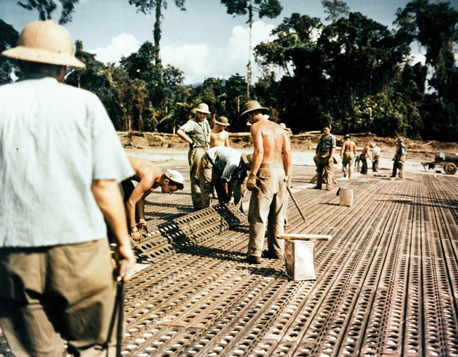 Seabees lay steel mats during the construction of a new bomber airfield on Bougainville, December 1943.
