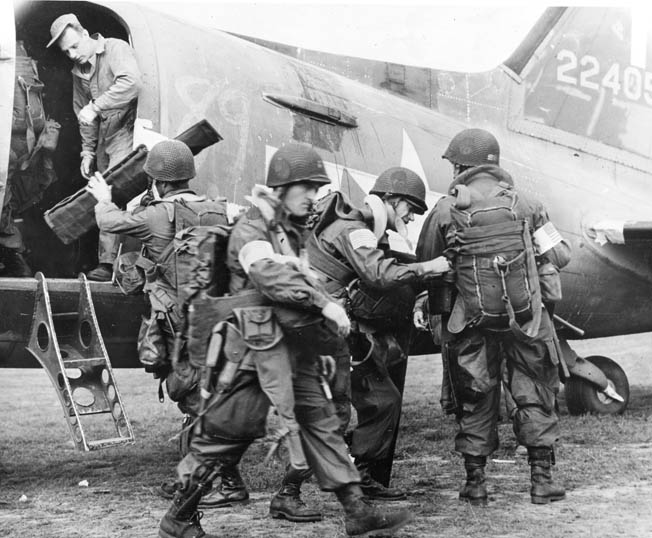 American paratroopers load gear and adjust their packs as they prepare to board a Douglas C-47 transport plane for the airborne invasion of Holland.