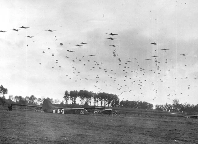 American paratroopers stream from their Douglas C-47 transport aircraft and begin their descent to an open field near the town of Grave, Holland. Gliders already litter the area after landing to disgorge men and supplies.