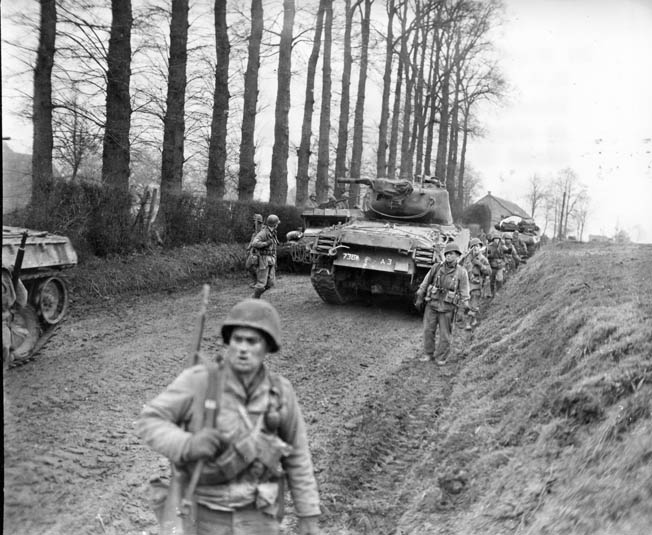 Infantrymen of the 83rd Division walk past Sherman tanks that have momentarily halted on a dirt road in Germany. This photo was taken in February 1945, and the war in Europe ended three months later.