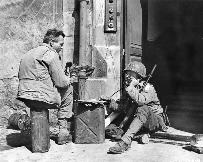 Situated in a doorway somewhere in France, a soldier operates mobile communications gear so that an officer can coordinate mortar fire during offensive operations. As a qualified lineman, Frank Fauver estimates he laid thousands of miles of communication wire for the Army.