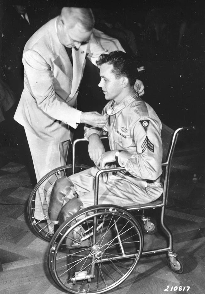 Confined to a wheelchair due to injuries sustained in combat, Sergeant Ralph Neppel of the 83rd Infantry Division receives the Medal of Honor from President Harry S. Truman.