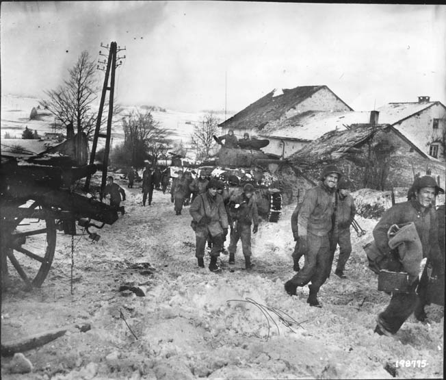 In this photo taken on January 11, 1945, soldiers of an 83rd Infantry Division reconnaissance unit trudge across the wintry landscape through the town of Bihain, Belgium, north of the crossroads town of Bastogne, which the Americans held against relentless German pressure.