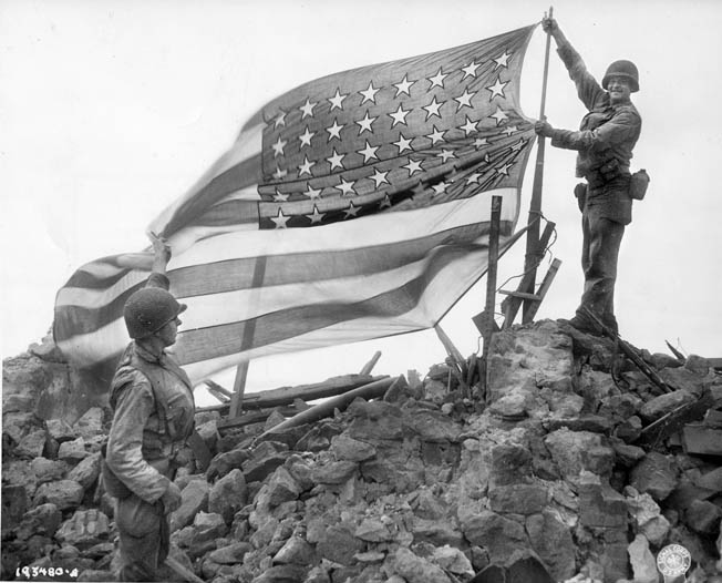After the German garrison on the island of Cezembre has surrendered, soldiers of the U.S. 83rd Infantry Division raise the American flag in triumph. The island is located near the French city of St. Malo, where troops of the 83rd Division were also engaged.
