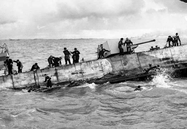 The crew of a Landing Craft, Gun (Medium) abandons ship after it was hit by German shore batteries during the landing of Royal Marines.