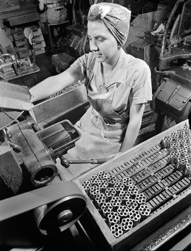 A woman works with a milling machine at one of the manufacturing facilities producing firearms for the military in World War II. The U.S. government awarded contracts to numerous firearms manufacturers, including Smith & Wesson and Colt.