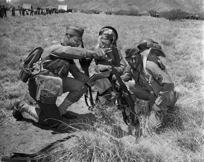 "Three members of Company M, 25th Regiment, 93rd Infantry Division—the first all-African American division in World War II—work out a field problem during training at Fort Huachuca, Arizona, May 1942. Although it had proven itself a competent combat force during World War I in France, the 93rd faced segregation and discrimination at home, and the War Department did not know what to do with it or other ""all-black"" units."