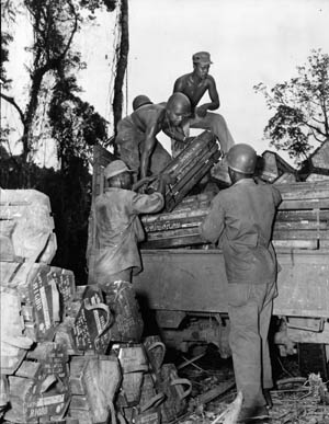 Members of the 593rd Field Artillery Battalion, an element of the 93rd Division, unload 105mm ammunition on Bougainville, April 1944. Because of widespread white prejudice against African American soldiers, many black units were assigned to perform menial labor.