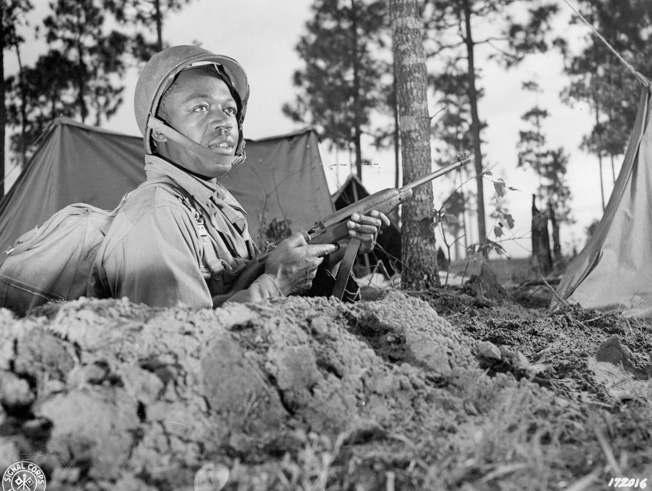Now outfitted with the modern M-1 helmet and an M-1 carbine, Private Clarence Jones, 594th Field Artillery Battalion, is photographed during the Third Army Louisiana Maneuvers, April 1943.