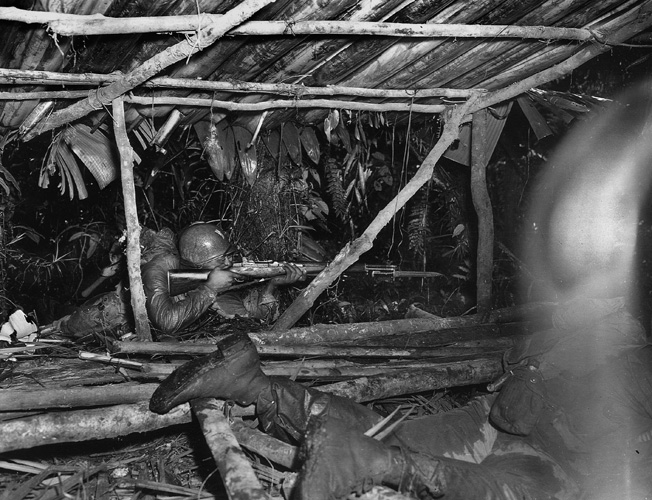 A 25th Infantry Regiment soldier, supporting the 23rd (Americal) Infantry Division, takes aim at Japanese troops in an enemy bivouac area on Bougainville, April 6, 1944.