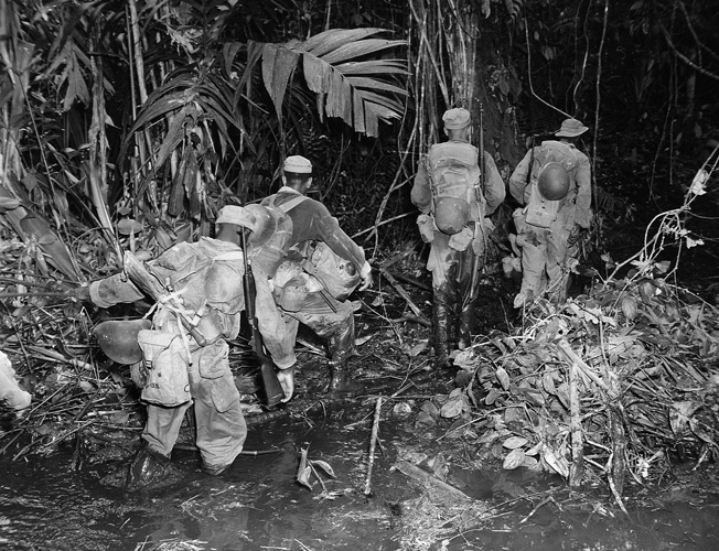 The hot, humid jungle conditions on Bougainville made combat an exhausting, harrowing experience for all troops. Here a patrol from the 25th Regiment slogs along a muddy, enemy-infested trail to reach their objective.