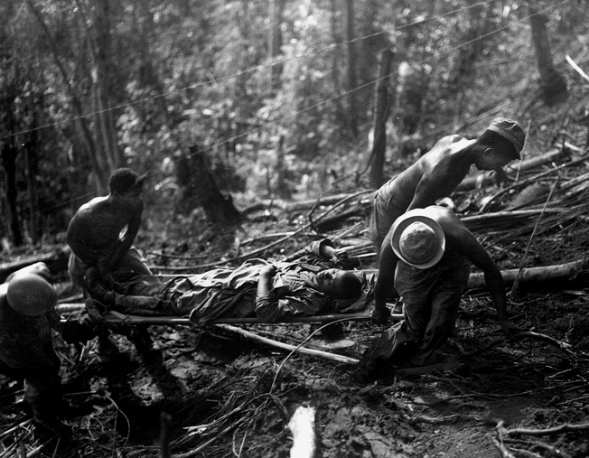 Litter bearers of Company K, 25th Regiment, 93rd Division struggle up Hill 290 on Bougainville with a wounded comrade during fighting on April 7, 1944.
