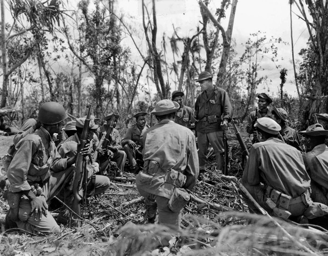 Members of the 1st Battalion, 24th Infantry are briefed by a white officer prior to heading out on a patrol in the Bougainville jungle, April 16, 1944.