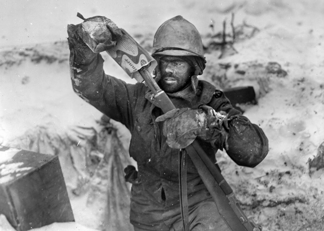 A soldier of the 99th Infantry Division covers the muzzle of his rifle during a lull in the fighting at Elsenborn Ridge. The remnants of the division were among the American troops that slowed the momentum of the German advance during the Battle of the Bulge, standing their ground in the face of the enemy onslaught.