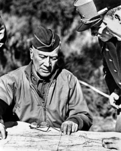 Major General Lloyd Fredendall converses with French officers in North Africa during a briefing.