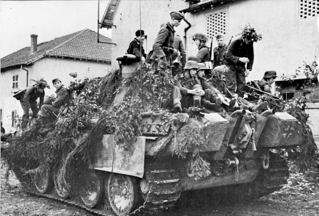 American Sherman tanks battle German Panthers blocking a minor intersection in St. Sever.