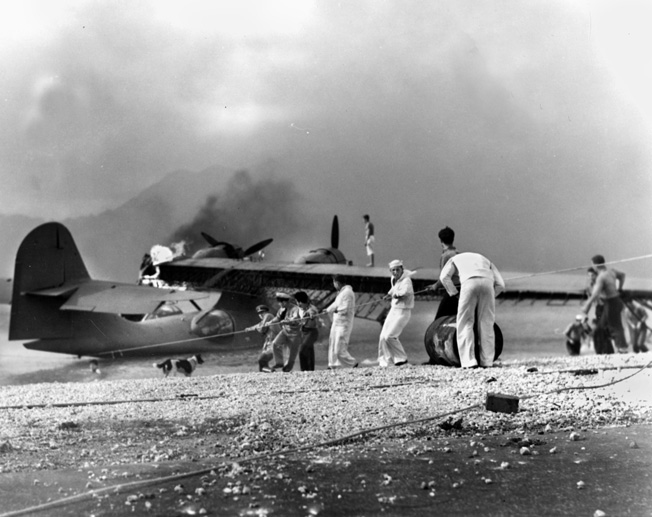 Sailors rush to save a burning PBY at Naval Air Station Kaneohe Bay. Construction work at the facility caught Yoshikawa's attention, and he went to great effort to reconnoiter the facility for the Imperial Japanese Navy.