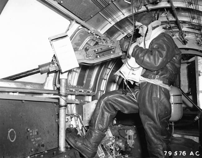 In a posed photo, a B-17 waist gunner shows his protective leather clothing and boots. The temperature in the drafty, unheated planes could drop to -60º F., and a round trip to Berlin from England could take eight hours.