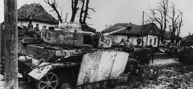 Advancing along a muddy road in the Ukraine during the winter of 1944, Soviet soldiers pause to take a look at a knocked-out German tank. This PzKpfw. VI Tiger has previously been fitted with additional armor skirting, but to no avail.