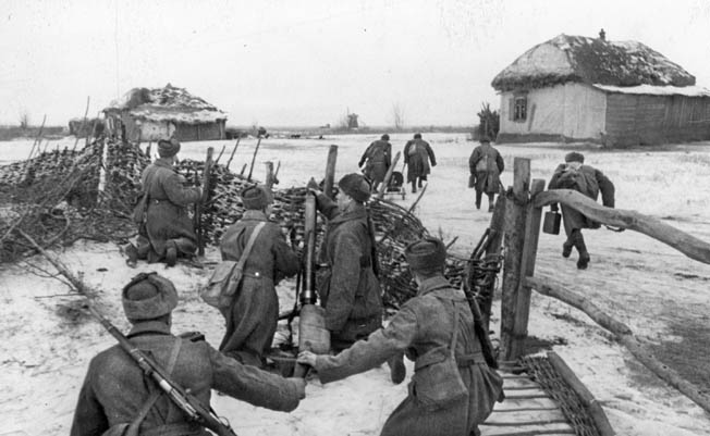 Soviet troops watch from behind a fence as their comrades rush a German-held farmhouse outside Stalingrad during the German rescue attempt, December 1942.