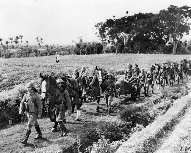 Dutch soldiers of the Royal Netherlands East Indies Army march toward a confrontation with the invading Japanese on Java. When enemy forces attacked, the Dutch offered stiff resistance but were compelled to retreat and eventually surrender.