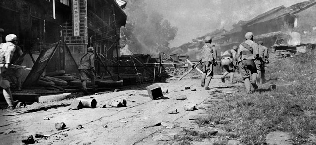 May 1944: Chinese troops advance through the streets of the ancient city of Tengchung, held by the Japanese for two years. The Japanese garrison at Tengchung was wiped out.
